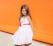 Fashion little girl posing in dress. Against colorful wall Royalty Free Stock Photo
