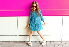 Fashion little girl posing in leopard print dress on colorful pink wall royalty free stock images