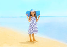 Fashion little girl in a striped dress and hat. Relaxing on the beach near sea, summer, vacation, travel - concept Royalty Free Stock Photography