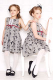 Fashion little girls. Posing in gray dresses Stock Photo
