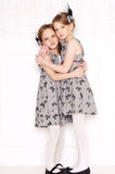 Fashion little girls. Posing in gray dresses Stock Photos