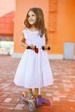 Fashion little joyful girl in dress. On the scooter near colorful mall Stock Photography