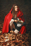 Fashion little red riding hood posing in the forest. With a crossbow  like an hunter Royalty Free Stock Image