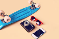 Fashion look concept. Blue skateboard, red sunglasses, vintage camera and screen smartphone. Trendy colorful photo Royalty Free Stock Photography