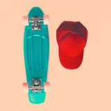 Fashion look concept. Skateboard and cap, top view. Vintage. Colors photo Royalty Free Stock Photography