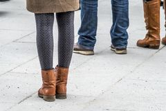 Fashion look of girl dressed in casual style in short skirt and broun boots. In the city square stock photo