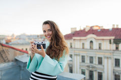 Fashion look, pretty cool young woman model with retro film camera. curly hair outdoors. Stylish girl photographer takes the old c royalty free stock photography
