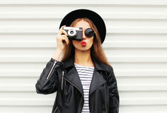 Fashion look, pretty cool young woman model with retro film camera wearing elegant black hat, leather rock jacket over white. Background Stock Photo