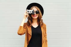 Fashion look, pretty cool young woman model with retro film camera wearing a elegant hat, brown jacket, curly hair outdoors Royalty Free Stock Image