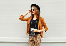 Fashion look, pretty cool young woman model with retro film camera wearing elegant hat, brown jacket outdoors over city background Royalty Free Stock Photo
