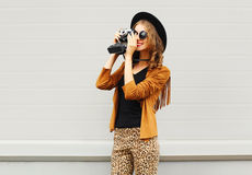 Fashion look, pretty cool young woman model with retro film camera wearing a elegant hat, brown jacket, in profile outdoors Royalty Free Stock Photography