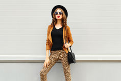 Fashion look, pretty woman wearing a retro elegant hat, sunglasses, brown jacket and black handbag over background. Fashion look, pretty woman wearing a retro Stock Images