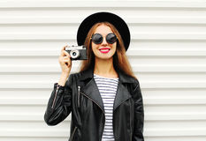 Fashion look, pretty young woman model with retro film camera wearing elegant black hat, leather rock jacket over white Royalty Free Stock Images