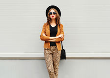 Fashion look, pretty young woman wearing a retro elegant hat, sunglasses, brown jacket and black handbag clutch stock photography