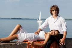 Fashion lovely beautiful couple. Sitting in the hot sun on the pier near the boats and yachts in summer. Young men and sensual brunette outdoor portrait in Royalty Free Stock Image