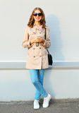 Fashion lovely young smiling woman using smartphone wearing coat handbag clutch in city Royalty Free Stock Images