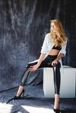 Fashion luxury blonde girl in man`s shirt. Sexy blonde slim fit woman with great body in lingerie underwear and in men`s white shirt in sexy, sensual, hot pose Stock Images