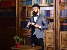 Fashion, luxury lifestyle, success, vintage concept. Aristocrat stands near bookcase with thoughtful face. Bearded man in elegant outfit in his cabinet. Rich stock images