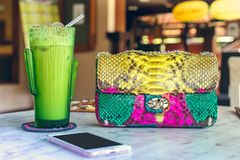 Fashion luxury snakeskin python handbag on the wooden table in restaurant. Bali island. Fashion luxury snakeskin python handbag on the wooden table in Royalty Free Stock Photography