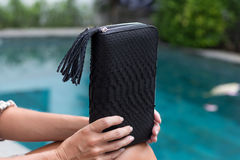 Fashion luxury snakeskin python wallet in woman hands sitting near the swimming pool, Bali. Fashion luxury snakeskin python wallet in woman hands sitting near royalty free stock images