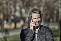Fashion macho smiling with smartphone in casual sweatshirt. Happy guy in hood talk on mobile phone on sunny outdoor. Bearded man s. Mile in hood on fresh air Royalty Free Stock Images