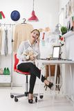 Fashion magazine editor in her office talking with smart phone. Young fashion woman with magazine royalty free stock image