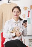 Fashion magazine editor in her office. Young fashion woman sending a message with smart phone royalty free stock image