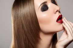 Fashion make-up & cosmetics. Beautiful model with red lips, straight hair Royalty Free Stock Photography