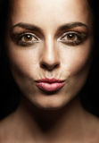 Fashion make-up. Glamourous portrait of beautiful young woman wearing evening professional makeup with glitter, kissing gesture Royalty Free Stock Photos