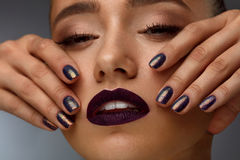 Fashion Makeup. Beautiful Woman With Dark Lips And Purple Nails. Fashion Woman Makeup. Closeup Portrait Of Beautiful Young Model Face With Long Eyelashes, Matte royalty free stock images