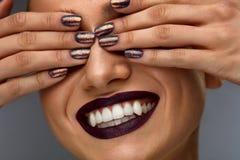 fashion makeup Kvinnan med mörker spikar, läppstift och vitleendet royaltyfria bilder