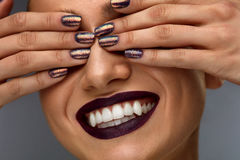 Fashion Makeup. Woman With Dark Nails, Lipstick And White Smile. Fashion Makeup. Closeup Of Beautiful Fashionable Woman Closing Eyes With Hands With Dark Glitter Royalty Free Stock Images