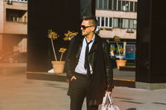 Fashion male model looking away and smiling in leather jacket ou Stock Photos