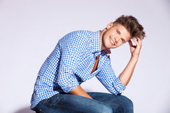 Fashion male model sitting and laughing. Blond fashion male model sitting and laughing on gray background Stock Photos