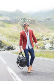 Fashion man with bag in hand outdoor. Picture of a young fashion man walking with a bag in his hand, on the middle of the road, in the mountains while looking Stock Photography