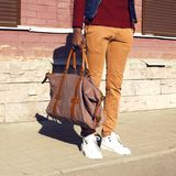 Fashion man with bag stands in city stock photography