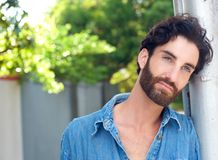 Fashion man with beard and blue shirt standing outdoors Stock Images