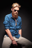 Fashion man in blue shirt and sunglasses sitting Stock Image