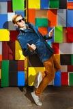 Fashion man on colorful brick wall stock photography