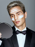 Fashion man with cosmetic cream treatment on his face, looking in the mirror. Stock Photography