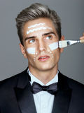 Fashion man with cosmetic cream treatment on his face. Royalty Free Stock Photography