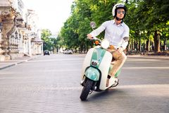 Fashion man driving a scooter Stock Photos