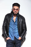 Fashion man with glasses and leather jacket posing royalty free stock images
