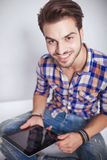Fashion man holding a tablet pad computer while smiling Royalty Free Stock Photos