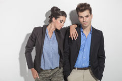 Fashion man leaning on a wall next to his girlfriend Royalty Free Stock Photo