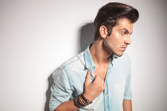 Fashion man leaning on a wall while pulling his collar. Side view of a young fashion man leaning on a wall while pulling his collar Stock Images