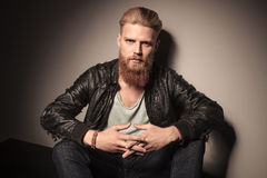 Fashion man in leather jacket. Fashion man with beard, in leather jacket, sitting and looking at the camera Royalty Free Stock Images