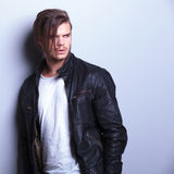 Fashion man in leather jacket looks away. From the camera while standing against a gray wall Royalty Free Stock Photos