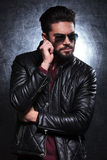 Fashion man in leather jacket and sunglasses pulling his beard Stock Image