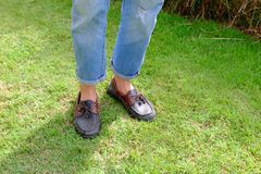 Fashion Man is Legs in Blue Jeans and Wear Vintage Shoes on Green Grass Background. Great for Any Use Stock Image